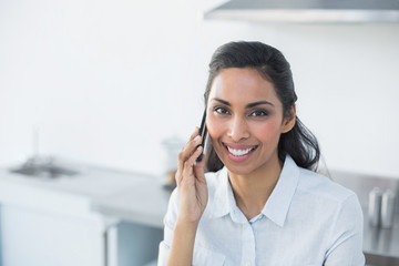 Content smiling woman phoning with her smartphone in bright kitc