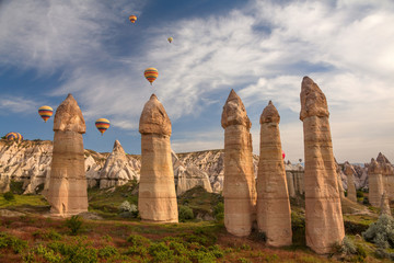 Hot air balloons flying over rock landscape at Cappadocia.