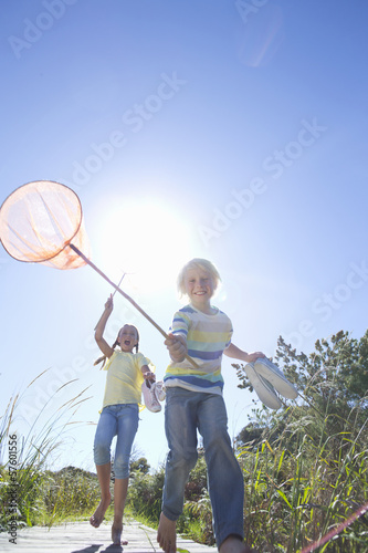 Enthusiastic boy and girl holding fishing nets