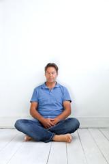 Mann im Schneidersitz meditierend auf dem Boden sitzend