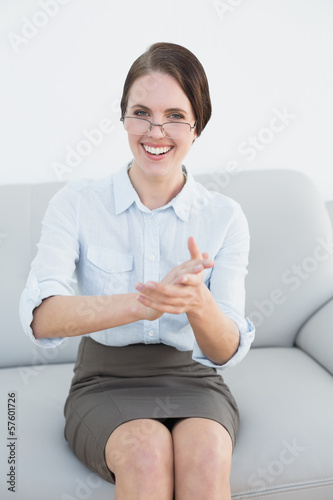 Smiling smart woman clapping hands on sofa