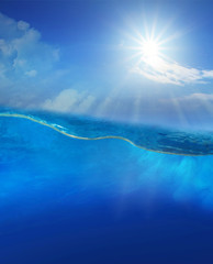 under blue water with sun shining above