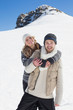 Couple in warm clothing against snowed hill