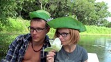 Young couple in hats of lotus leaf rolls around in a boat