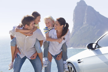 Happy family piggybacking outside car near ocean