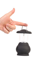 Hand holds camping lantern.
