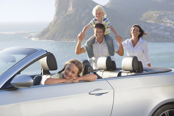 Portrait of happy family with convertible near ocean