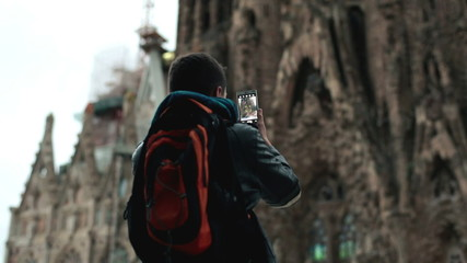Boy taking picture with his cellphone in the city