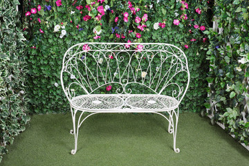 Beautiful retro bench near to  verdant hedge with small flowers.