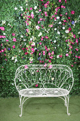 Beautiful white bench stands near to green hedge