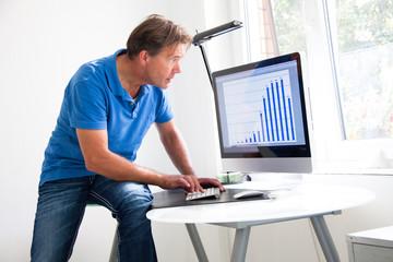 Mann schaut Diagramm auf dem Monitor an