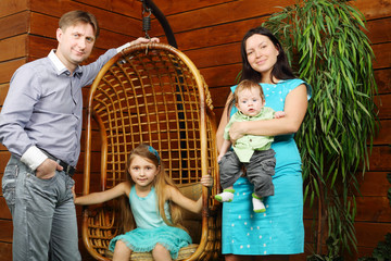 Little girl sits in wicker hanging chair and father, mother