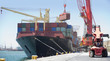 Crane unloading container ship at commercial dock