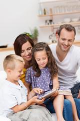 eltern und kinder schauen auf tablet
