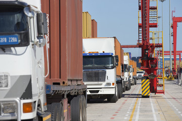 Lorries with cargo containers at commercial dock