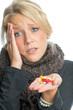 Blonde Frau mit einer Handvoll Tabletten