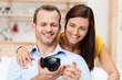 lächelndes paar schaut auf digitalkamera