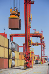 Crane lifting cargo container at commercial dock