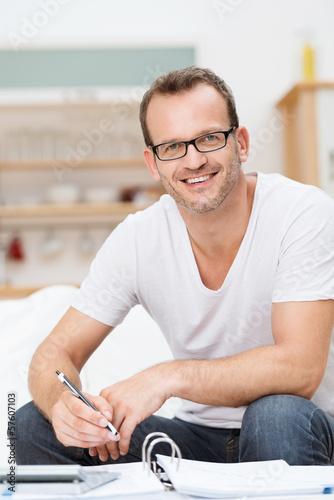 mann mit aktenordner und taschenrechner zu hause