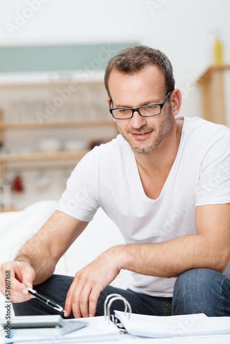 mann prüft unterlagen mit taschenrechner