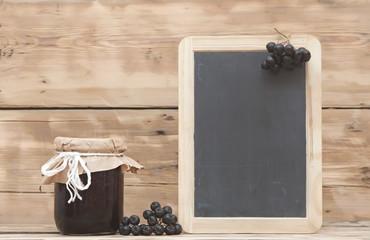 Black chokeberry jam on wooden table