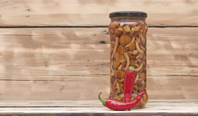 Mushrooms marinaded (agaric honey) in glass jar with red chili p