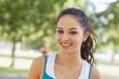 Portrait of cute sporty woman posing in a park