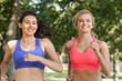 Two beautiful sporty women jogging in a park