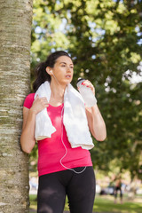 Beautiful sporty woman drinking water and leaning against a tree