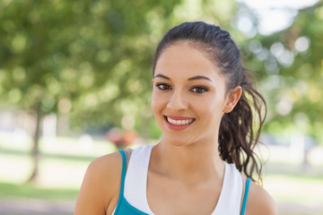 Portrait of cute sporty woman posing in a park