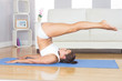 Sporty slim woman doing yoga pose on blue exercise mat