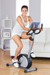 Happy training woman using an exercise bike while holding a tabl