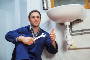 Handsome plumber sitting next to sink showing thumb up