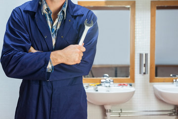 Plumber in blue boiler suit posing with wrench