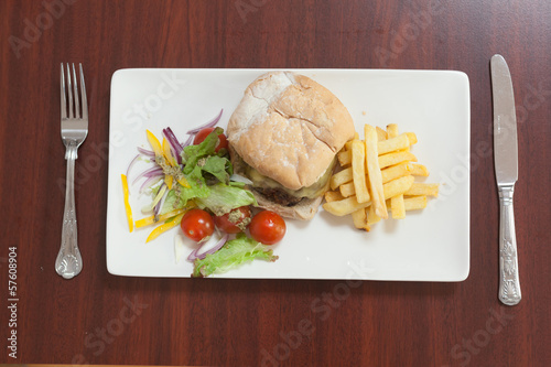Overhead view of burger with french fries and salad