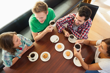 Four smiling students having a cup of coffee chatting
