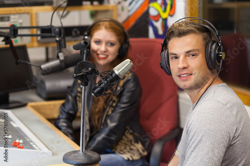 Attractive cheerful radio host interviewing a guest - 57609155