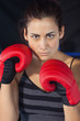 Close-up of a beautiful woman in red boxing gloves