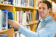 Smiling mature student selecting book from shelf in library