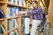 Disabled wheelchair selecting book in library