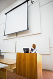 Teacher with computer and projection screen in lecture hall