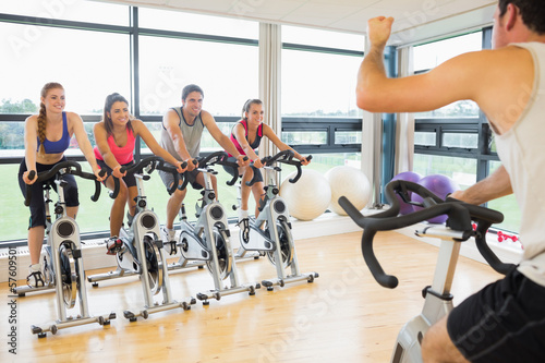 Man teaching spinning class to four people