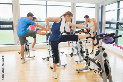 People warming up by exercise bikes in spinning class