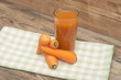 Glass of carrot juice and ripe carrots on colorful napkin