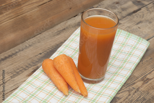 Glass of carrot juice and carrots on colorful napkin