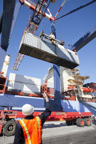 Worker guiding crane with cargo container at commercial dock