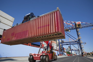 Mobile crane moving cargo container at commercial dock