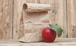 apple with paper bag on a wooden background