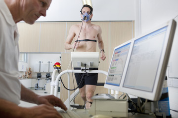 Sports scientist at computer and runner with mask on treadmill in laboratory