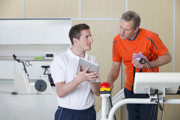 Sports scientist with digital tablet talking to runner on treadmill in laboratory